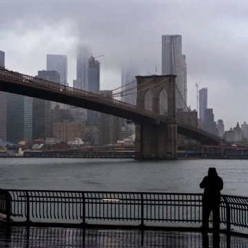 Image: A passersby on Brooklyn side of the East River faces the rain and clouds as they loom over lower Manhattan