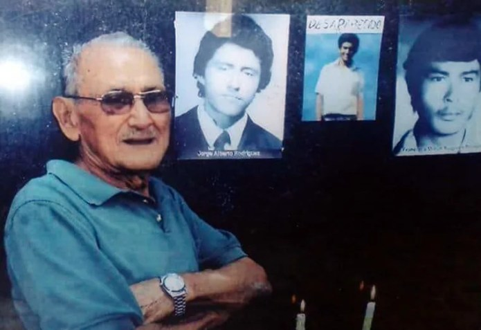 Image: Francisco Meliton Rodriguez Sequiera next to the monument where photos of victims of the disappeared are displayed in San Salvador