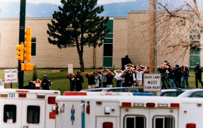 Students are escorted out of Columbine High School by police after a shooting on April 20, 1999.