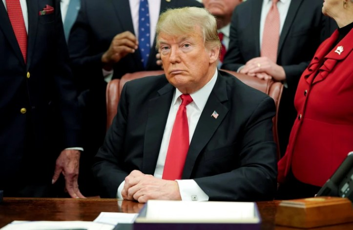 Image: President Donald Trump listens to questions from reporters in the Oval Office of the White House on Dec. 21, 2018.