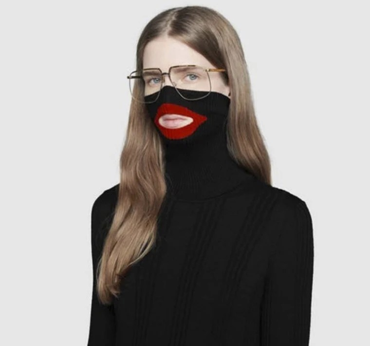 Image: An online fashion outlet showing a Gucci turtleneck black wool balaclava sweater for sale, that they recently pulled from its online and physical stores
