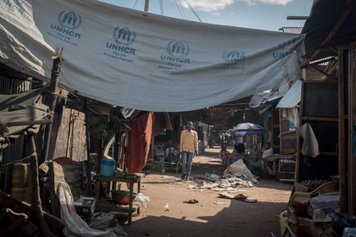 Image: A refugee walks under a UNHCR awning in Dadaab.