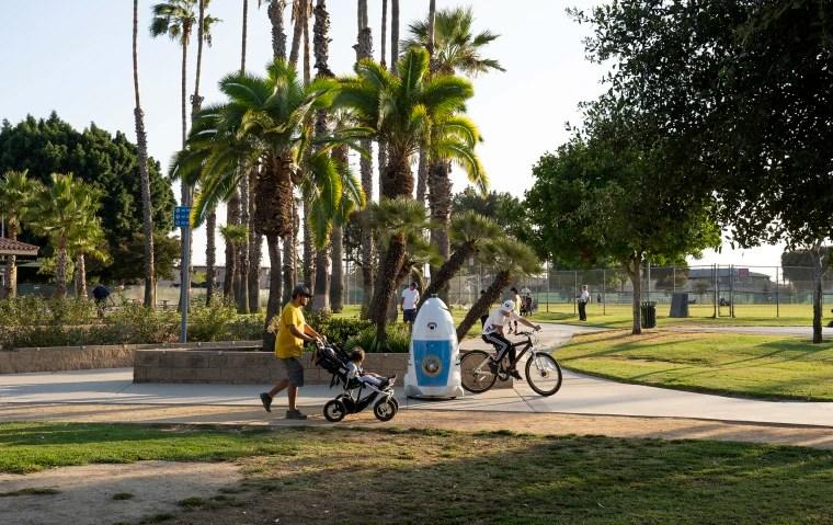 People ride past HP RoboCop in Salt Lake Park, Los Angeles on Sept. 19, 2019.