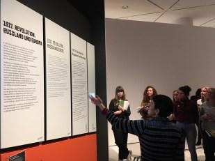 """Brigitte Vogel vom DHM in der Ausstellung """"1917. Revolution"""" erklärt den Aufbau der Raumtexte in deutscher, englischer, leichter Sprache sowie auch Braille und Video in deutscher Gebärdensprache."""