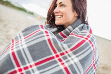 Media Bakery ID: WAV0133154 Side view of a smiling young woman covered with blanket at the beach