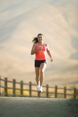 Attractive female runner running next to a fence.