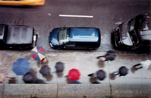 People with umbrellas on street, elevated view (blurred motion)
