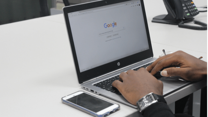 A person is typing on an open laptop with Google search bar on the screen. A smartphone is next to the laptop.