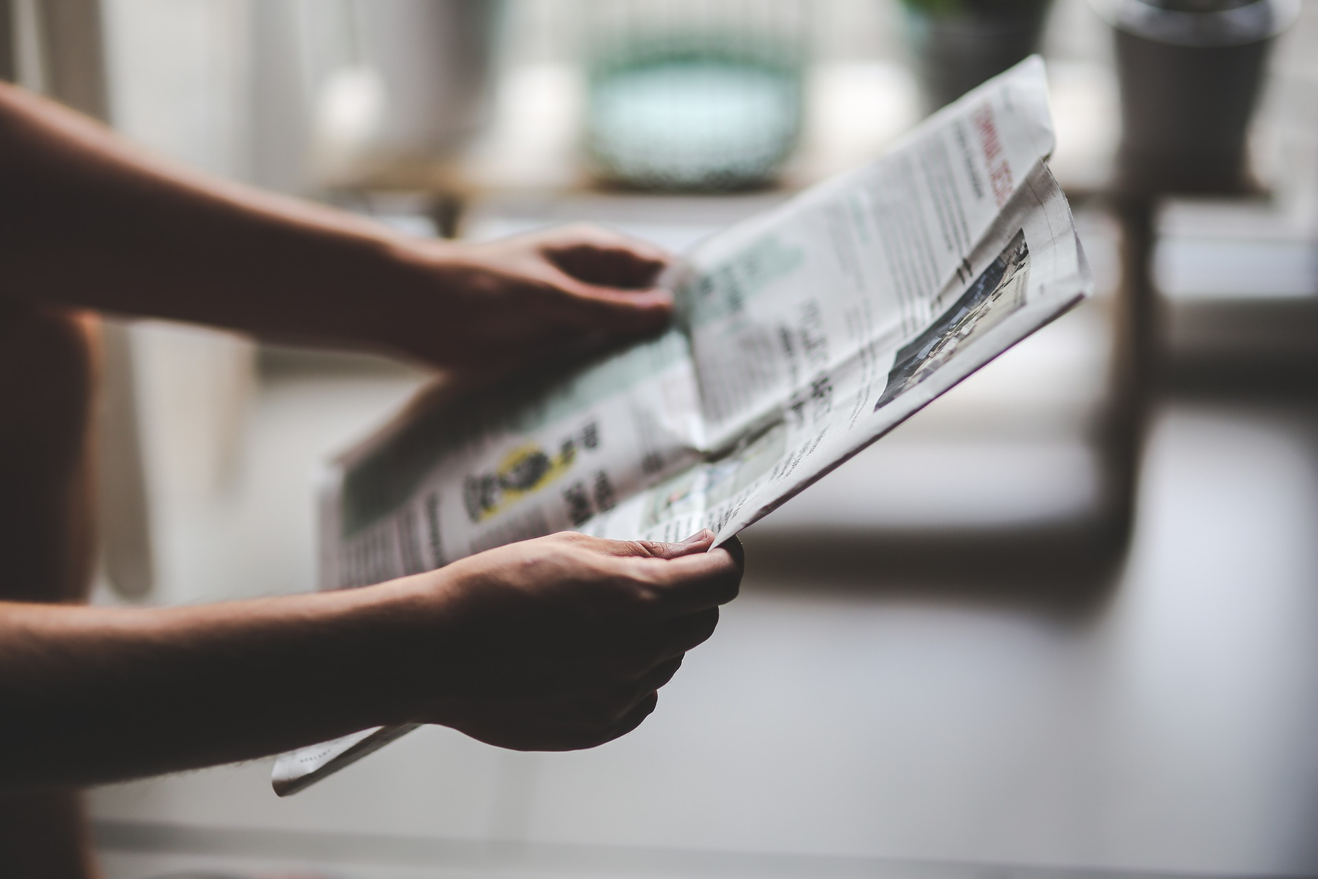 Person holding up a newspaper