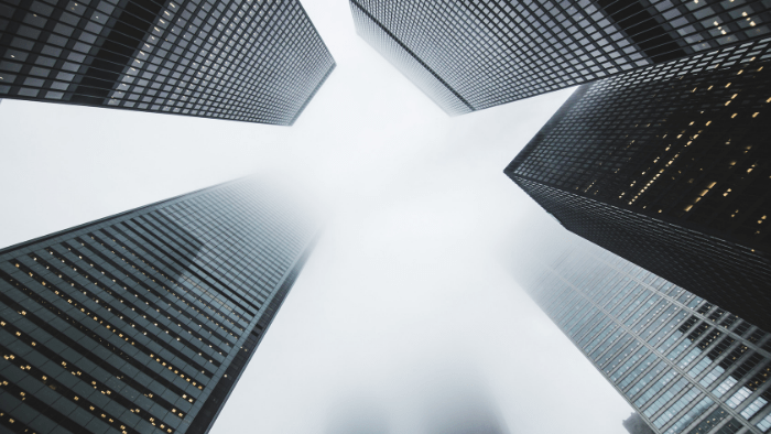 Media Insider 1.10: View from the ground, looking up at skyscrapers partly covered by clouds.
