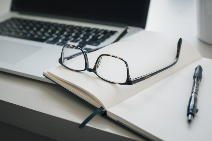 Glasses sitting on an open notebook with a pen and laptop also on the table