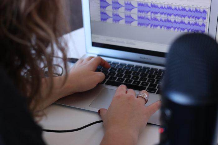 Woman using MacBook Air to edit audio files
