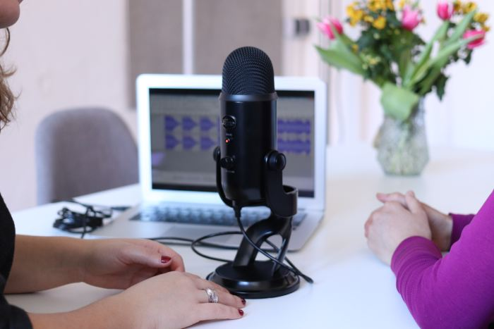 Two people sitting on either side of a microphone with an open laptop in the background