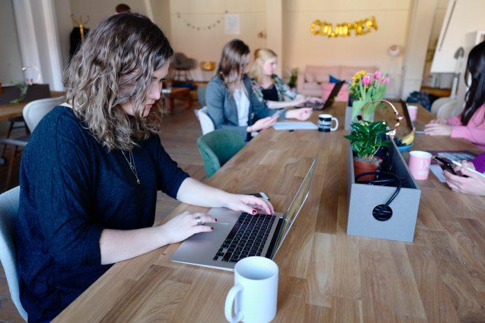 Women working at a shared desk in a CoWomen office