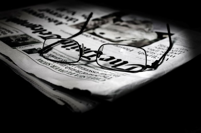 Glasses laying on top of a folded newspaper
