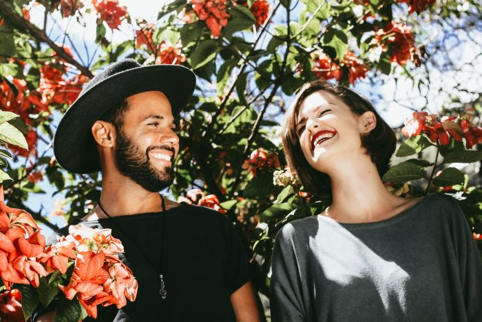 Couples Photography Tips - couple smiling in front of red and green floral trees