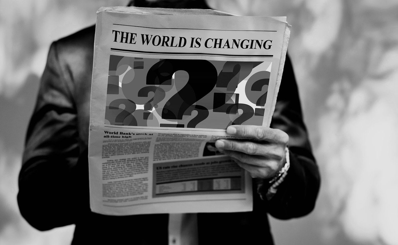 "Man reading a newspaper with ""The World is Changing"" headline"