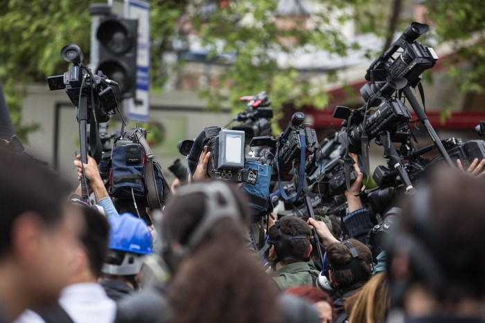 photo of a crowd of media personnel holding up cameras