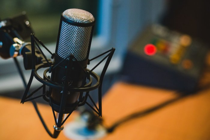 a podcast microphone on a table with podcast equipment behind it