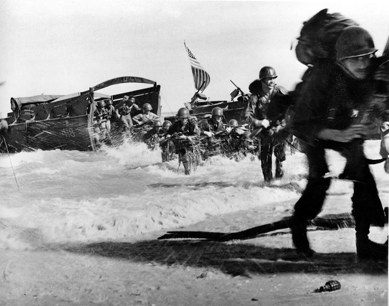 Description of  May 1944: The first wave of U.S. Infantrymen leave their higgins boats and race through the surf for the beach during the invasion of Wakde Island, Dutch New Guinea during World War II. (AP Photo/U.S. Army Signal Corps)
