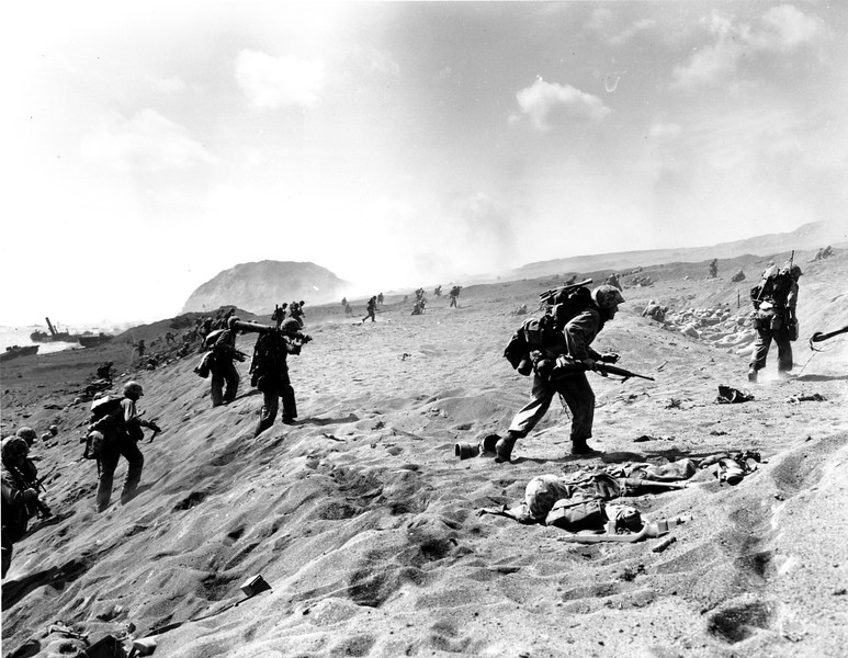 Description of  Feb. 19, 1945: U.S. Fourth Division Marines move in from the beach on Iwo Jima, the Japanese Volcanic Island. A dead Marine lies at right in the foreground. Mt. Suribachi, in the background, was turned into a beehive of guns by Japanese troops. It was scaled by the U.S. Marines, who took control. (AP Photo/Joe Rosenthal)