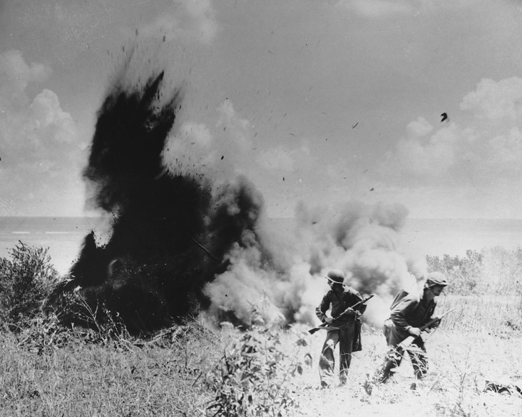 Description of  July 1944: U.S. Marines walk away from a Japanese foxhole after blowing it up with explosives, during the invasion at Saipan, in the Mariana Islands.  (AP Photo)