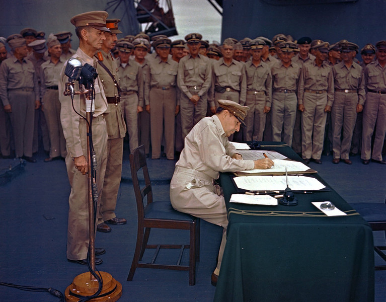 Description of  September 2, 1945: Gen. Douglas MacArthur signs the Japanese surrender documents aboard the USS Missouri in Tokyo Bay. Lt. Gen. Jonathan Wainwright, left foreground, who surrendered Bataan to the Japanese, and British Lt. Gen. A. E. Percival, next to Wainwright, who surrendered Singapore, observe the ceremony marking the end of World War II. (AP Photo)