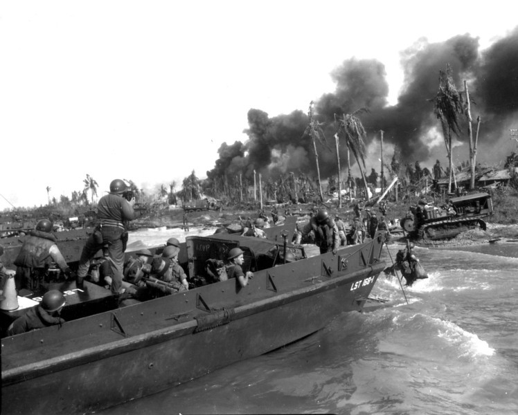 Description of  July 1945: Australian troops storm ashore in the first assault wave to take Balikpapan on the southeast coast of oil-rich Borneo. Standing in the LST, Coast Guard Combat Photographer James L. Lonergan is documenting the landing operations. (AP Photo)