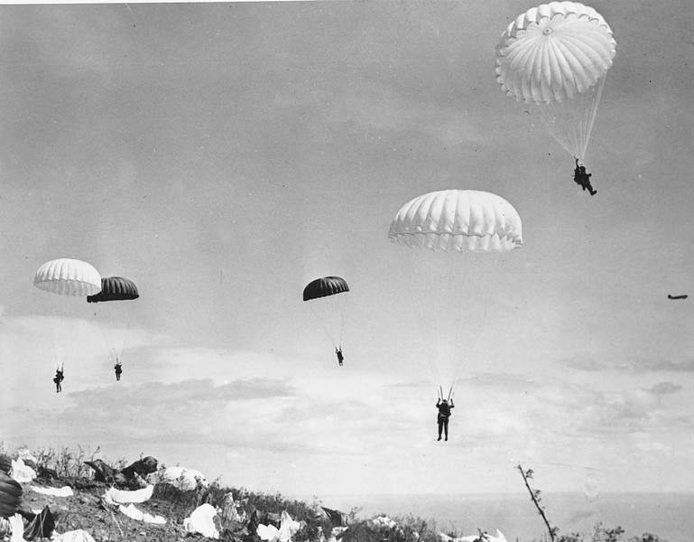 Description of  Feb. 1945: U.S. paratroopers of the 503rd Paratroop Regiment float to earth on Corregidor, a rocky island strategically located at the entrance of Manila Bay on Luzon Island, Philippines during World War II. (AP Photo/U.S. Army Signal Corps)
