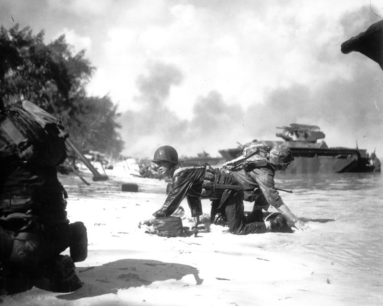 Description of  June 1944: Two U.S. Marines are seen crawling to their assigned positions under enemy fire on the beach at Saipan, Mariana Islands. (AP Photo)