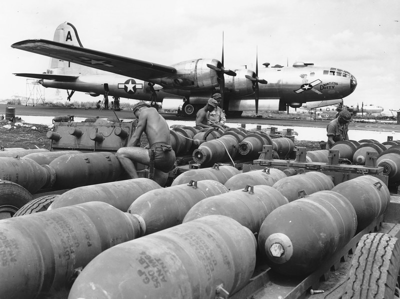 Description of  November 1944: Ground crew members prepare bombs to be loaded into the racks of the waiting B-29 Superforts, at a U.S. airbase on Saipan, in the Mariana Islands. (AP Photo)