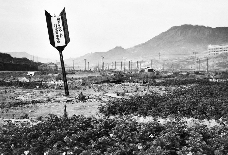 Description of  August 10, 1945: An arrow marks the spot where the A-bomb struck at Nagasaki, Japan. Much of the bombed area is still desolate, the trees on the hills in the background remained charred and dwarfed from the blast and little reconstruction, except of wooden shacks as homes, has taken place. (AP Photo)