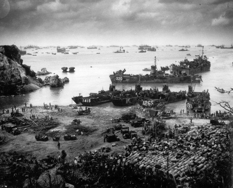 Description of  April 13. 1945: About 350 miles from the Japanese mainland, U.S. invasion forces establish a beachhead on Okinawa island. Pouring out war supplies and military equipment, the landing crafts fill the sea to the horizon, where stand the battleships of the U.S. fleet. (AP Photo)