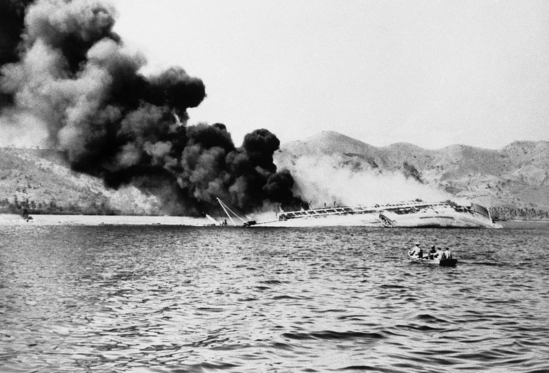 Description of  August 3, 1942: After hammering Port Moresby for two days, Japanese bombers finally sank this Australian transport which sends up a cloud of smoke. She drifted onto a reef and heeled over. Flaming oil can be seen at left. The men in a small boat, foreground, are looking for victims. (AP Photo)