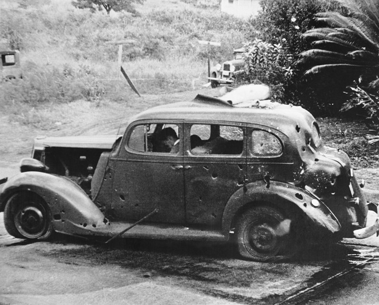 Description of  December 7, 1941: Eight miles from Pearl Harbor, shrapnel from a Japanese bomb riddled this car and killed three civilians in the attack. Two of the victims can be seen in the front seat. The Navy reported there was no nearby military objective. (AP Photo/U.S. Navy)