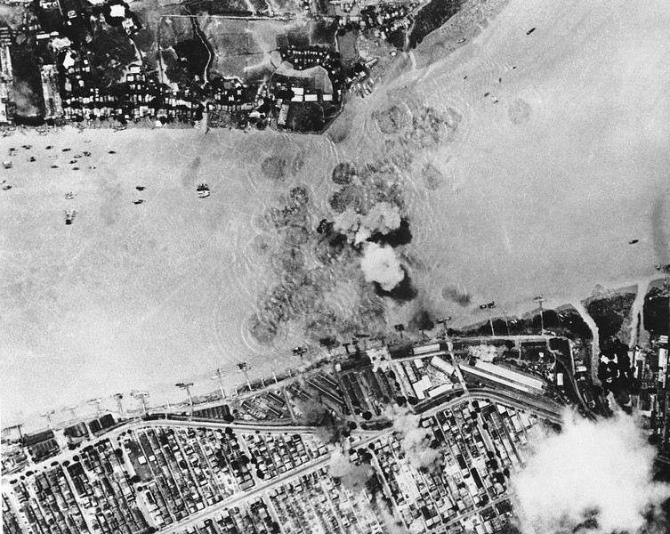 Description of  Nov. 11, 1943: A supply ship, one of two that the Japanese were able to work through U.S. Air attacks, explodes in Rangoon Harbor (center) after a direct hit by a bomb from a Tenth U.S. Air Force Plane. Hits also were scored on port facilities, seen smoking (top center). Note numerous small craft moored at docks and offshore, (right). (AP Photo)