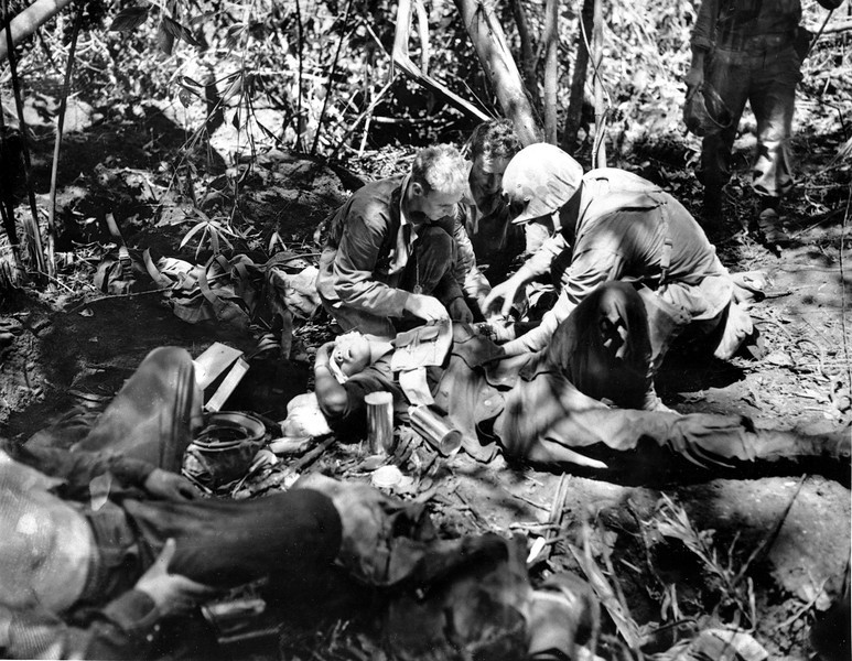 Description of  February 1944: A wounded marine receives treatment from a Navy medical corpsman at a jungle first aid station behind the lines on New Britain Island, New Guinea, in the Battle for the Strategic Japanese air field on Cape Gloucester during World War II. (AP Photo/U.S. Marine Corps)