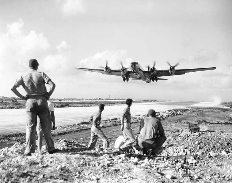 Description of  December 1944: U.S. soldiers at the Saipan airbase, in the Mariana Islands, watch as a B-29 Superfortress takes off for an air raid on the Japanese mainland. (AP Photo)