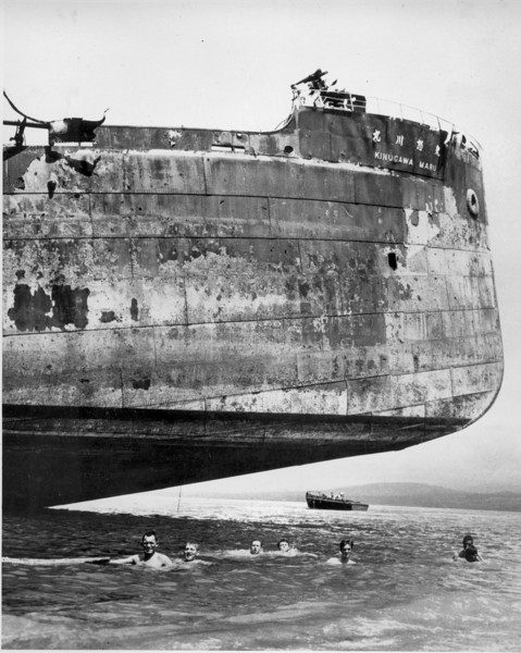 Description of  Nov. 11, 1943: Crewmen of a U.S. Coast Guard combat transport go for a swim under the hull of a Japanese landmark in the Solomon Islands during World War II. The boat is the Kinugawa Maru, beached by the Japanese after being riddled by American gunners. Coast guardsmen took part in the original invasion of the Solomons.  (AP Photo)