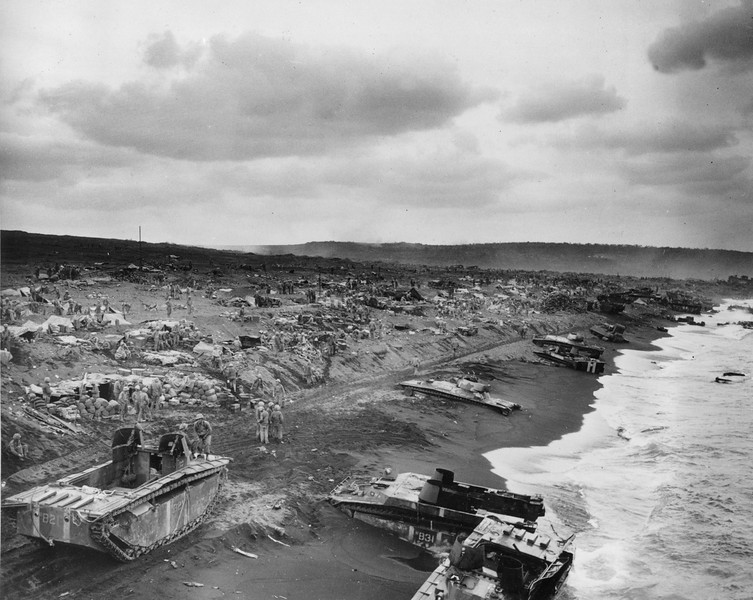 "Description of  Feb. 1945: This general view shows amtracs bogged down in the sands along the beaches of Iwo Jima after the American invasion of the Japanese stronghold during World War II. In the background, U.S. Marines and Coast Guard beach parties operate communications and command posts and fox hole ""hospitals"" as assault troops push back the enemy from established beaches on the Volcano Island. (AP Photo/U.S. Coast Guard)"