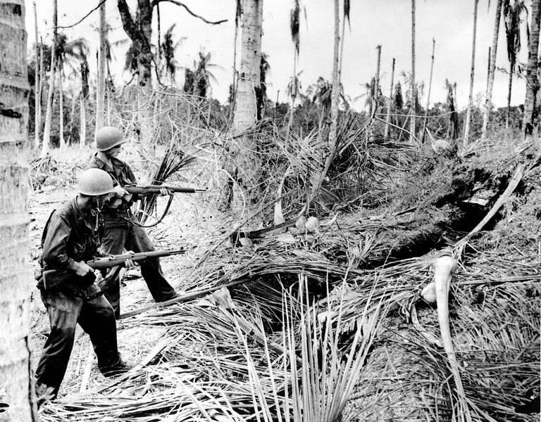 Description of  January 1943: Two American soldiers of the 32nd Division cautiously fire into a Japanese dugout before entering it for inspection during a drive on Buna, which resulted in a defeat of Japanese forces in the Papaun peninsula of New Guinea during World War II. (AP Photo/U.S. Army Signal Corps)