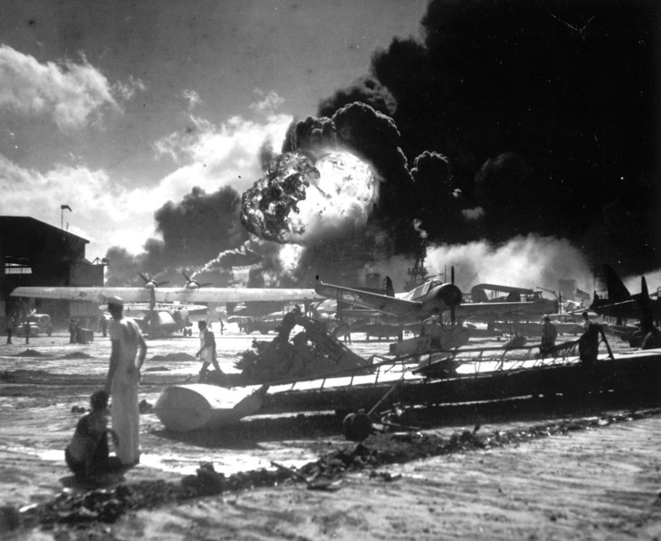 Description of  December 7, 1941: Sailors stand among wrecked airplanes at Ford Island Naval Air Station as they watch the explosion of the USS Shaw in the background, during the Japanese surprise attack on Pearl Harbor, Hawaii. (AP Photo)