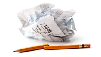 picture of crumpled tax form and broken pencil