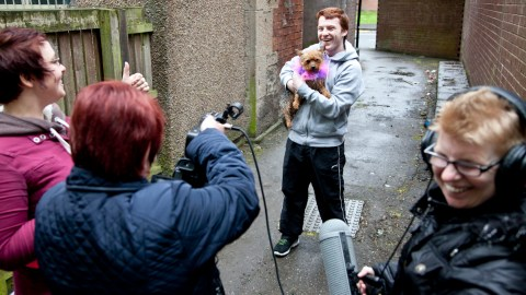 Participants filming outside, guy holding a dog, all smiling and having fun
