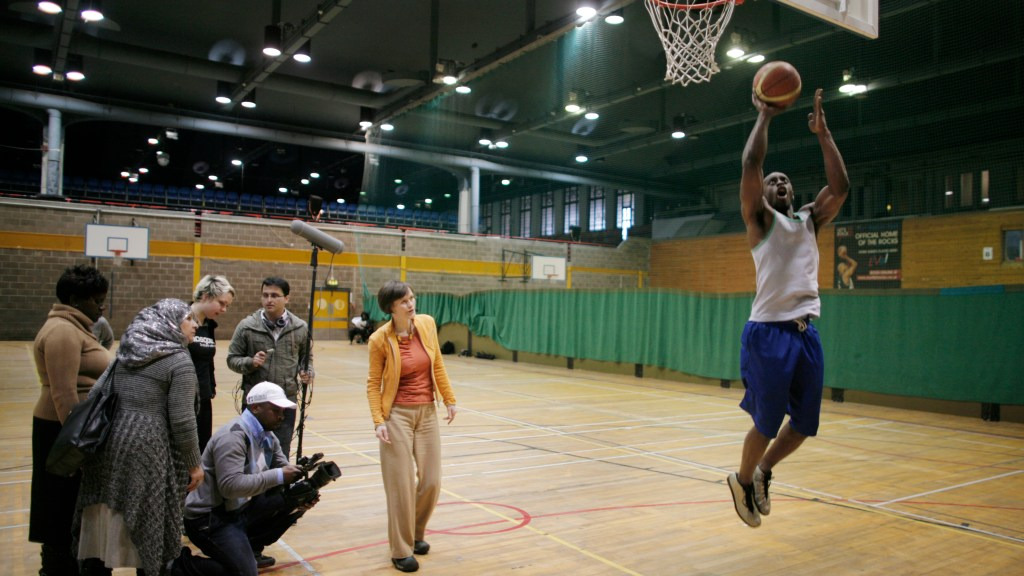 Basketball player taking a shot with production participants and camera to the side