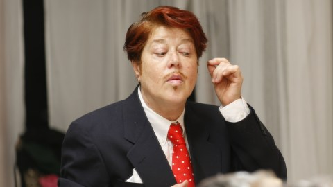 Diane Torr dressed in a suit and appearing to be doing her make-up