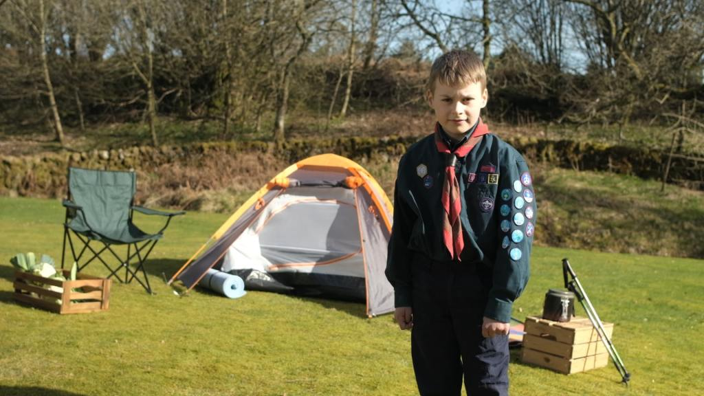 A boy in a Scout uniform stands in his garden surrounded by camping equipment.