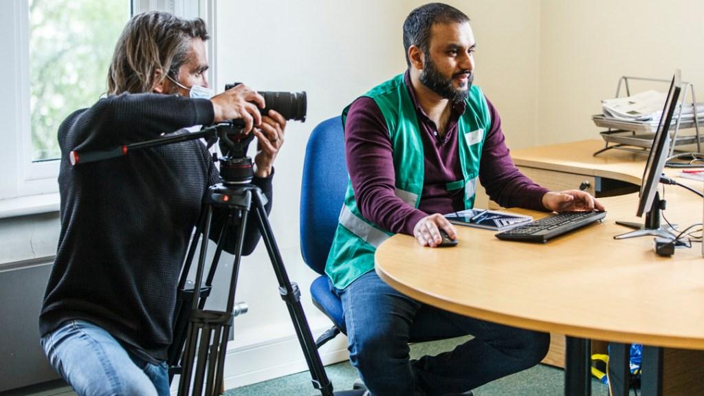 A man in an office films a man wearing a green vest in an office.