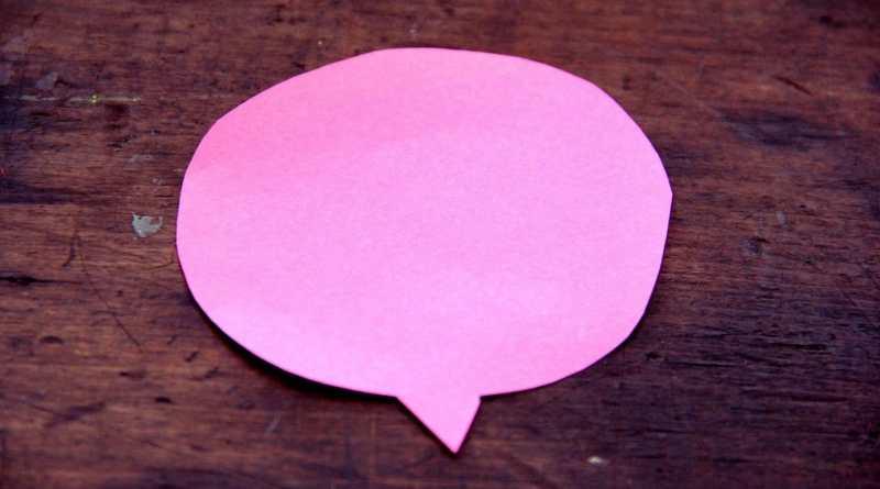 Bulle de discussion, phylactère de BD rose, sur fond bois