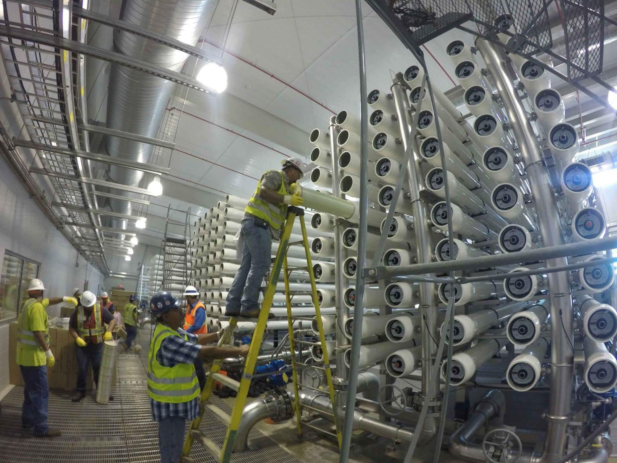 hight resolution of workers install filters at a saws desalination facility in south bexar county